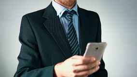 Il movimento lento, un uomo d'affari in un vestito alla moda utilizza uno smartphone video d archivio