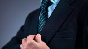 Il movimento lento, un uomo d'affari in un vestito mette il telefono in sua tasca video d archivio