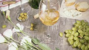Il movimento lento versa in un bicchiere di vino fra la vista superiore dei fiori e degli spuntini archivi video