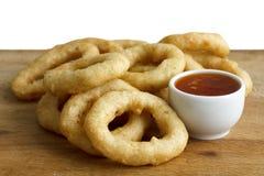Il mucchio degli anelli fritti nel grasso bollente dei calamari o della cipolla con i peperoncini rossi immerge sul wo Fotografia Stock