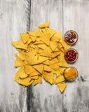 Il mucchio dei nacho del cereale scheggia con le varie immersioni su fondo di legno rustico, vista superiore fotografia stock libera da diritti
