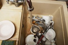 Il mucchio dei piatti sporchi gradisce i piatti, le tenaglie vaso della carne e la coltelleria nel lavandino beige leggero del gr Fotografie Stock Libere da Diritti
