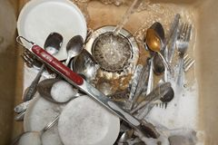 Il mucchio dei piatti sporchi gradisce i piatti, le tenaglie vaso della carne e la coltelleria nel lavandino beige leggero del gr Fotografia Stock