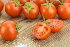 Il mucchio dei pomodori ciliegia con uno ha tagliato nella metà e nel pizzico di sale Fotografie Stock