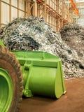 Il mucchio del residuo di metallo ed il grande bulldozer dentro riciclano la fabbrica, Tailandia Fotografia Stock