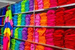Il mucchio delle magliette colourful piegate copre di un negozio Fotografie Stock