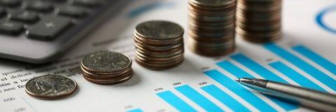 Il mucchio delle monete d'argento sta alle carte millimetrate finanziarie fotografia stock libera da diritti
