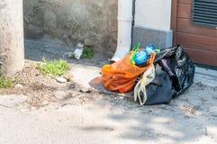 Il mucchio di immondizia e di ciarpame domestico ha lasciato nella parte anteriore della casa nella via nei sacchetti di plastica Immagini Stock