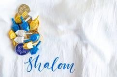Il mucchio di oro e di argento Chanukah conia con i dreidels minuscoli su un panno di tela bianco Fotografia Stock Libera da Diritti