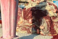 Il mucchio di rete da pesca con rosso galleggia su Greco Immagine Stock