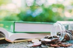 Il mucchio di soldi conia nel barattolo di vetro con i libri su natur vago Immagine Stock Libera da Diritti