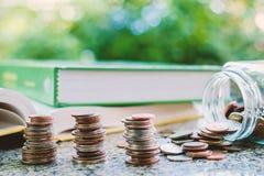 Il mucchio di soldi conia nel barattolo di vetro con i libri su natur vago Immagini Stock