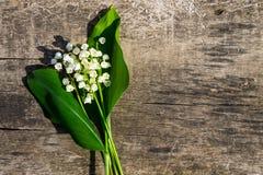 Il mughetto fiorisce su fondo di legno con lo spazio della copia Fotografia Stock