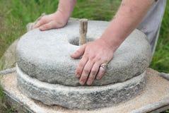 Il mulino di pietra antico del grano della mano Le mani del ` s degli uomini girano una mola di pietra Immagine Stock