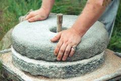 Il mulino di pietra antico del grano della mano Le mani del ` s degli uomini girano una mola di pietra Fotografie Stock