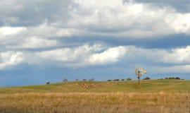Il mulino a vento su un pendio di collina della California sotto una nube ha riempito il cielo Fotografie Stock Libere da Diritti