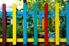 Il multi arcobaleno colorato di legno recinta il giardino immagine stock
