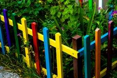 Il multi arcobaleno colorato di legno recinta il giardino fotografia stock