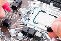 Il multimetro di uso dell'ingegnere a riparare la scheda madre del computer immagini stock