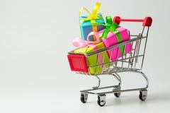 Il multiplo colora i regali in un carrello immagine stock