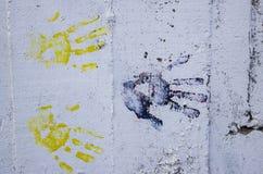 Il multiplo ha colorato le stampe della mano sulla parete sporca bianca Immagini Stock Libere da Diritti