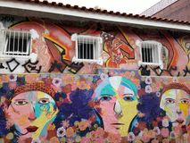 Il murale variopinto di arte della via circa il fumetto della gente con il fiore multiplo modella fotografia stock