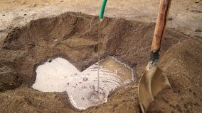 Il muratore aggiunge l'acqua di rubinetto alla miscela di calcestruzzo per fare la malta liquida video d archivio