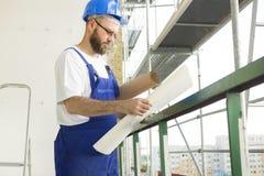Il muratore in attrezzatura funzionante ed in casco sta ad elevata altitudine sul cantiere Fotografie Stock