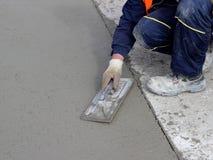 Il muratore conclude il bordo della superficie di calcestruzzo Fotografia Stock