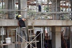 Il muratore della costruzione di edifici che fa intonacando il lavoro che sta sull'armatura convoglia agli impianti immagine stock libera da diritti