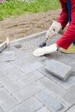 Il muratore dispone i blocchetti di calcestruzzo della pietra per lastricati per l'accumulazione del patio, facendo uso del marte Immagine Stock Libera da Diritti