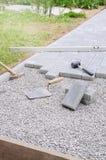 Il muratore dispone i blocchetti di calcestruzzo della pietra per lastricati per l'accumulazione della a Immagini Stock Libere da Diritti