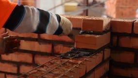Il muratore fa una parete del mattone rosso video d archivio