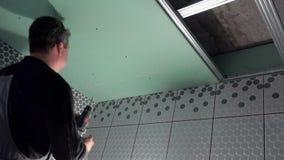 Il muratore monta il soffitto ed il muro a secco di riparazione con il cacciavite video d archivio