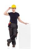 Il muratore si appoggia il cartello in bianco Immagine Stock