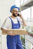 Il muratore sorridente nel lavoro equipaggia e casco sulla testa che parla sul telefono Lavoro ad elevata altitudine Armatura nel Fotografie Stock