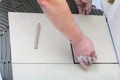 Il muratore sta piastrellando a casa, adesivo della pavimentazione in piastrelle fotografia stock