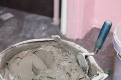 Il muratore sta piastrellando a casa l'adesivo della pavimentazione in piastrelle immagini stock