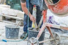 Il muratore sta pulendo una pala Fotografia Stock Libera da Diritti