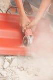 Il muratore sta tagliando il tetto di mattonelle Immagini Stock