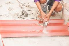 Il muratore sta tagliando il tetto di mattonelle Fotografia Stock