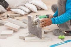 Il muratore sta tagliando le mattonelle grige della pavimentazione Fotografia Stock