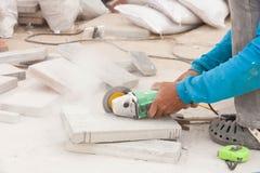 Il muratore sta tagliando le mattonelle grige della pavimentazione Immagine Stock Libera da Diritti