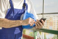 Il muratore in un abbigliamento del lavoro tiene un numero del casco, del telefono cellulare e del quadrante della costruzione di Fotografia Stock