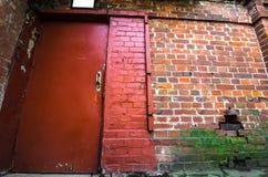 Il muro di mattoni rosso ed il ferro a porta chiusa immagine stock