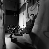 Il muscolo aumenta l'allenamento d'oscillazione dell'uomo degli anelli alla palestra Fotografie Stock Libere da Diritti