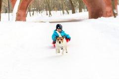 Il musher sorridente del bambino ed il suo cane di slitta che si divertono all'inverno parcheggiano Fotografia Stock Libera da Diritti
