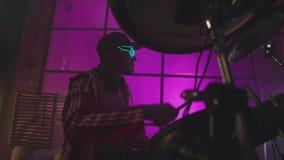 Il musicista alla moda gioca i tamburi in uno studio di colore azione Uomo intelligente alla moda che gioca i tamburi video d archivio
