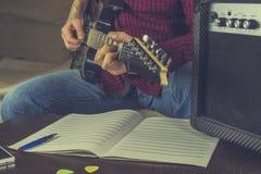 Il musicista dei pantaloni a vita bassa si siede sullo strato e gioca la chitarra elettrica Fotografia Stock Libera da Diritti