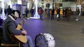 Il musicista della via nel centro di Mosca canta e gioca la chitarra ed i tamburi stock footage